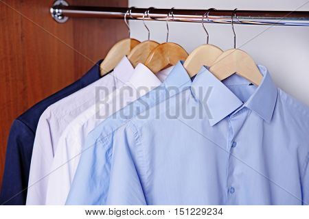 Hangers with male shirts on clothes rail in wardrobe