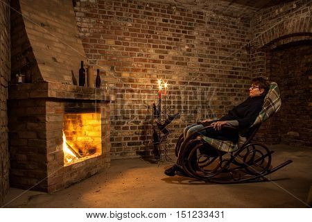 Woman in rocking chair by the fireplace in brick room and candles