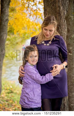 Pregnant mother with daughter on walk at autumn Park