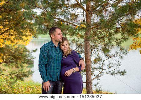 Happy pregnant family walking in autumn Park