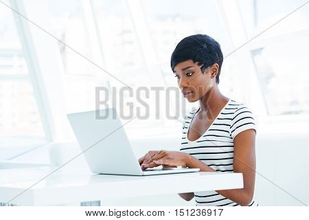 Serious african american businesswoman sitting with laptop at the table in office