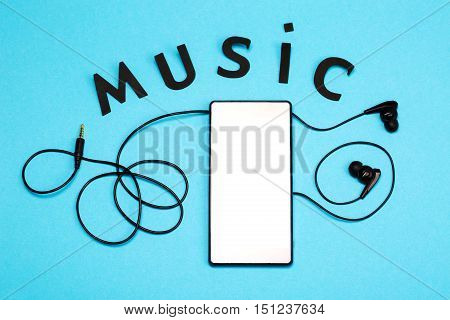 Black headphones and smart pnone on bright blue bakground. Concept of living with music. Lettering MUSIC like a part of composition