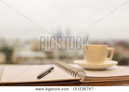 Closeu up of coffee cup spiral notepad and pen on blurry city background