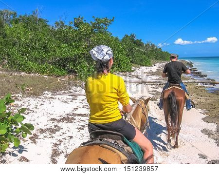 Bayahibe, Dominican Republic - May 26, 2006: tourists on horseback along the coast of the Parque Nacional del Este, Dominican Republic. Horse riding is an activity very practiced in Bayahibe.