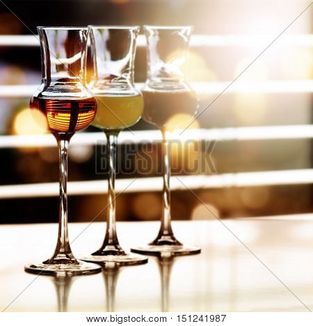 Different alcoholic drinks in front of a window with sun reflexes