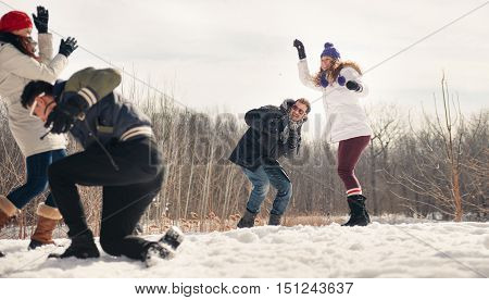 Group of millenial young adult friends throwing snowballs in wintertime in a snow filled park poster