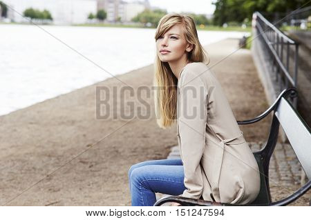 Thoughtful young woman on bench by river