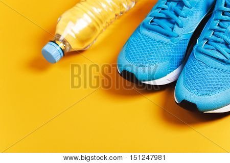 Blue sneakers and bottle of water on yellow background. Concept of healthy lifestile, everyday training and force of will.