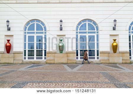 An unidentified executive in Luxembourg hurrying up along foreside of an administrative building with glassy vase sculptures in front of it - Luxembourg City, Luxembourg (Grand Duchy of Luxembourg), April 3 2015