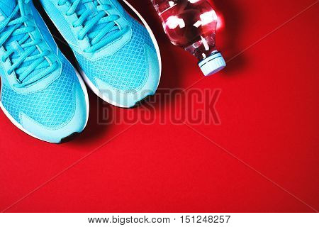 Blue sneakers and bottle of water on red background. Concept of healthy lifestile, everyday training and force of will.