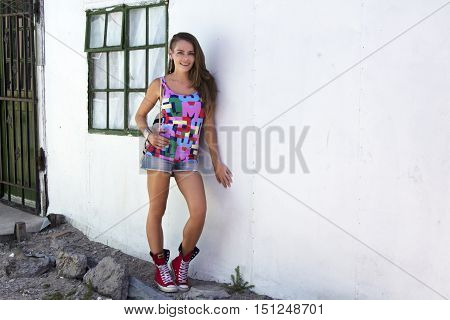 Caucasian female leaning against a township house in Africa