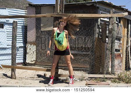 Caucasian female having fun tossing her hair about while standing in the street of an African township