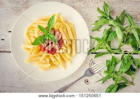Italian Wholemeal Pasta Penne with Tuna and Basil. Fresh pasta with tuna and tomato sauce on white wooden background. Baked penne pasta with tuna fish and tomato sauce. Italian food concept. Top view.