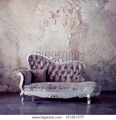 Beautiful sofa in classical style on a background of textured walls