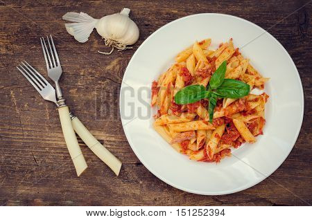 Italian Wholemeal Pasta Penne with Tuna and Basil. Fresh pasta with tuna and tomato sauce on old wooden background. Italian cuisine concept. Top view.