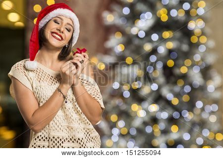 Christmas Gift. Smiling Beautiful Woman In Red Hat And Scarf Envisioning With Closed Eyes What Is In