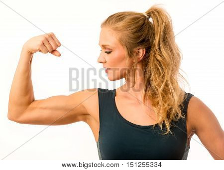 Fitness model posing proudly with arm muscle flexed