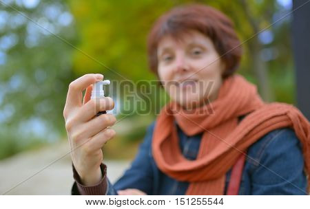 Young woman using throat spray in cold season