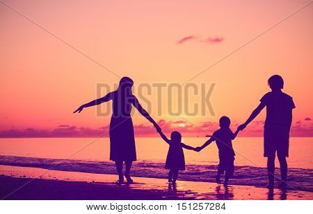 happy family with two kids walking at sunset sky