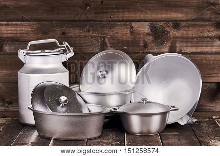 Different cast aluminium pots, pans and water-can on old grunge wooden table against wood wall background
