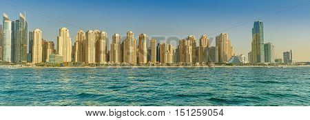 DUBAI, UAE - OCTOBER 09, 2016.  Panoramic skyline of the popular Jumeirah Beach Residence (JBR) in Dubai marina with turquoise waters of the Arabian Gulf