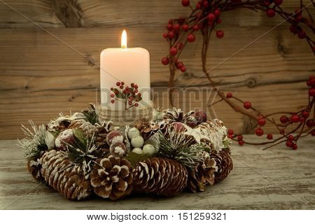 Elegant centerpiece for the Christmas table with a candle on a natural wreath