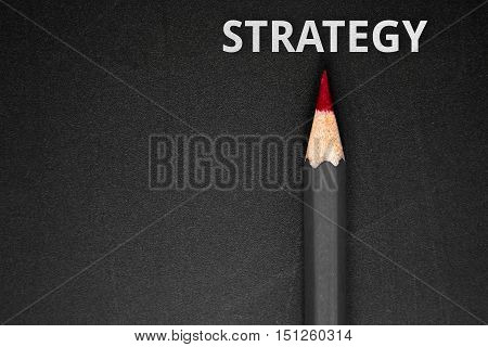 Text Strategy with pencil on black background / business concept