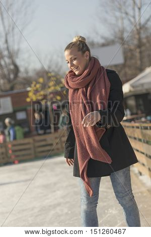 Young woman wearing warm winter clothes enjoying a beautiful sunny winter day on the ice rink skating and having fun