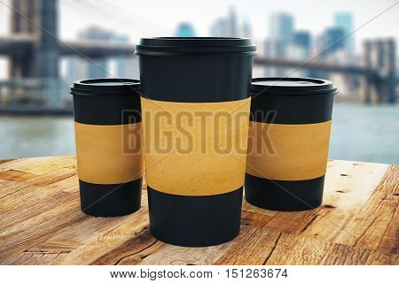 Close up of three black take away coffee cup with blank brown paper holder placed on wooden table. Modern city background. Mock up 3D Rendering