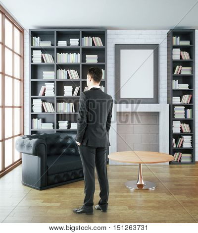 Back view of young businessman in luxurious library interior with black leather sofa bookshelves fireplace table and blank picture frame on white brick wall. Mock up 3D Rendering