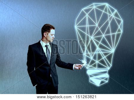Handsome young businessman drawing abstract polygonal light bulb on textured grey background. Idea concept