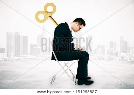 Businessman with wind up key on his back sitting on chair and using laptop computer on city background. Manipulation concept