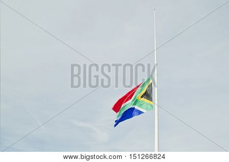 South african flag flown at half mast on a blue sky background