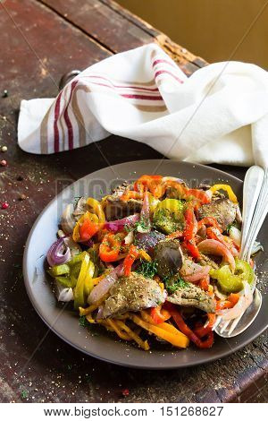 Warm salad with chicken liver, sweet bell pepper, onion in a plate, selective focus