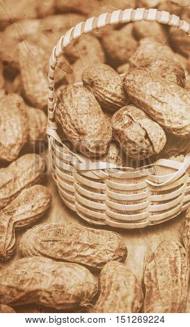 Closeup toned image of peanuts in small wicker basket. Groundnuts still-life