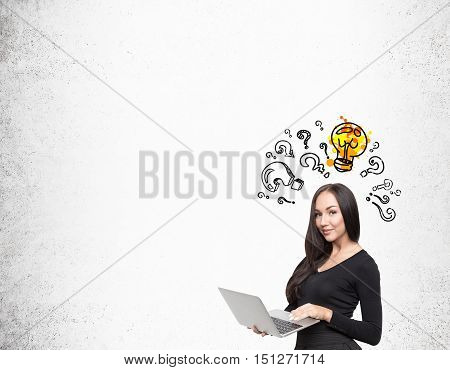 Girl with computer standing near concrete wall. Light bulb is shining above her head surrounded by question marks. Mock up