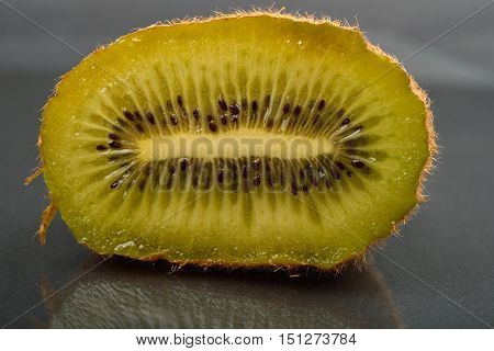 Close Up Of Half Kiwi With Wizened Skin On Dark Reflection Background. Natural Organic Vegetarian Fo