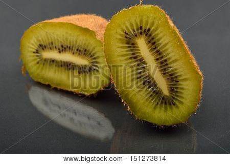 Close Up Of A Kiwi Cut In Two With Wizened Skin On Dark Reflection Background. Natural Organic Veget