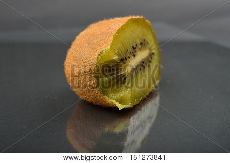Close Up Of A Half Of Kiwi Which Was Bitten With Teeth With Wizened Skin On Dark Reflection Backgrou