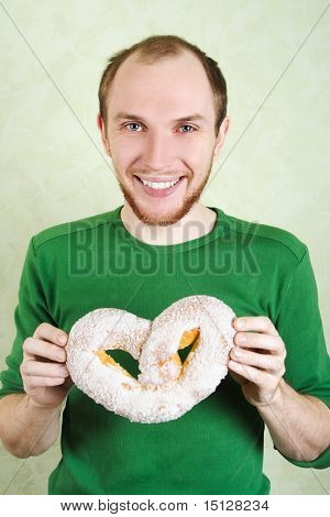 Man In Green Shirt Holding Big Pretzel With White Topping And Smiling