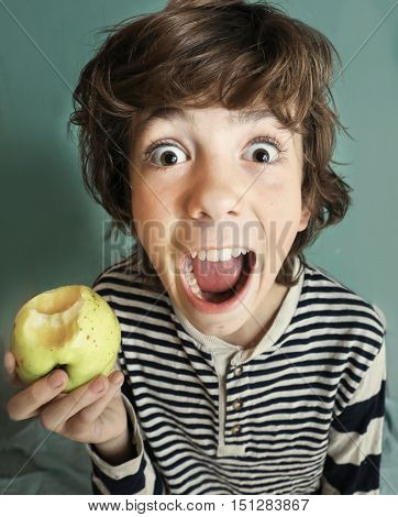 boy with strong white teeth bite apple close up photo on blue wall background