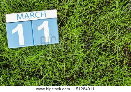 March 11th. Day 11 of month, calendar on football green grass background. Spring time, empty space for text.