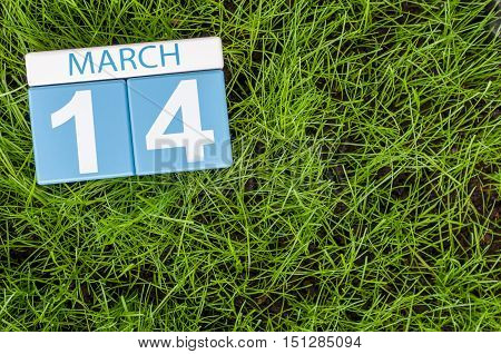 March 14th. Day 14 of month, calendar on football green grass background. Spring time. Commonwealth and International pi days.