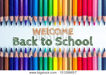 Text Welcome back to school on color pencil background