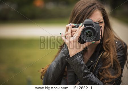 Young woman holding a professional DSLR camera and taking a photo