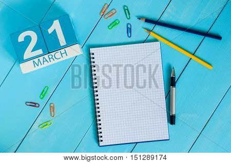 March 21st. Day 21 of month, calendar on blue wooden table background with notepad. Spring time, empty space for text.