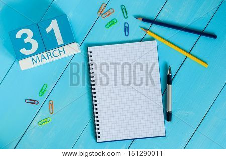 March 31st. Day 31 of month, calendar on blue wooden table background with notepad. Spring time, empty space for text.