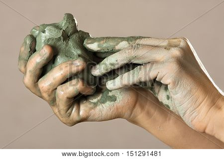 hands of potter holding raw blue clay