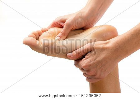 Macro close up of therapist doing foot massage. Isolated on white background.