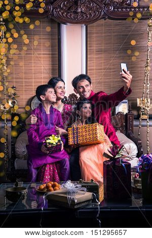 Asian Indian family taking selfie or self photograph at home with gift boxes on diwali festival. Parents and children indoor lifestyle. Indian family celebrating diwali and taking selfie on phone
